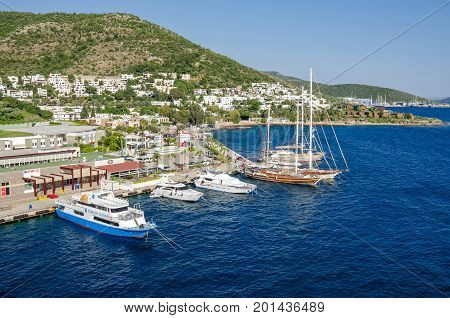 Bodrum Turkey - June 1 2017: View of the white city of Bodrum from the sea with the Gulet type schooners (a two-masted wooden sailing vessel) popular for tourist charters ferry and motorboats.