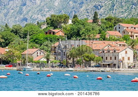 Kotor Montenegro - June 8 2017: Dobrota coast of the Bay of Kotor. A part of the waterfront that consists of a long line of stone villas and a small beach.