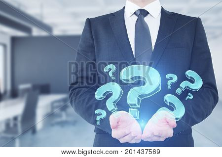 Businessman holding abstract glowing question marks in blurry office interior. Confusion concept.