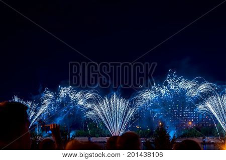Unrecognizable Silhouettes of people watch and shoot fireworks at night. New Year holiday celebration, display, festive background, place for writing text