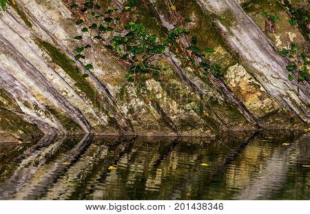Monolithic wall of rock covered with moss and ivy reflected in the water of the lake river