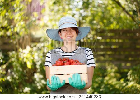 Agronomist in hat with tomato