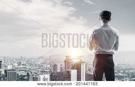 Young elegant businessman with arms crossed on chest looking away