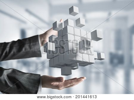 Cropped image of businessman hands holding multiple white cubes in hands. Mixed media.