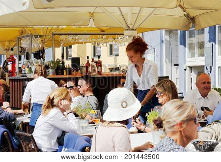Copenhagen Denmark - August 24 2017: Guests and staff at the outdoor seating at a restaurant in the district of Nyhavn.