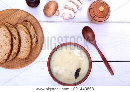 Cream mushroom soup with champignons on a white wooden table top view