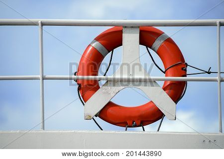 life belt life buoy red rescue ring on a white railing of a cruise ship against the blue sky with clouds insurance concept with copy space