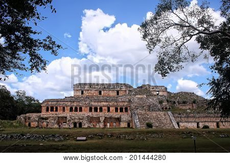 A panoramic view of the old multi-storey Mayan building in the town of Sayil in the Puuc region in Yucatan. Mexico with a background of blue sky and clouds daylight horizontal