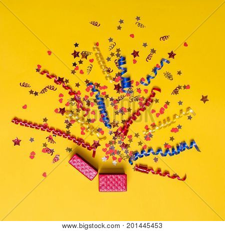 Creative concept with festive decor on yellow background. Confetti hearts and stars, red, yellow, blue ribbons fly out of the red gift box. Explosion of confetti.