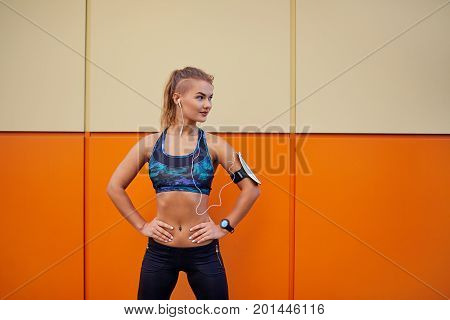 Girl sports listening smiling to music with headphones on orange background.