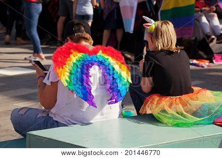 SOUTHAMPTON UK - August 26 2017: Southampton Pride 2017 City's second annual Pride event in Southampton UK. Mother wearing rainbow fairy wings sitting with daughter wearing a rainbow skirt. Rainbows symbolizing Pride.