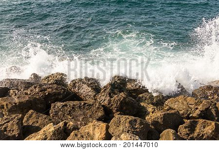 Azure sea white wave is broken about the shore brown stones greece crit