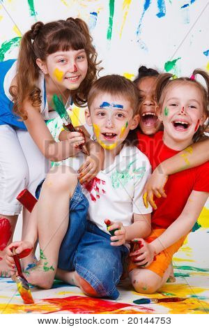 Laughing kids having fun with paints