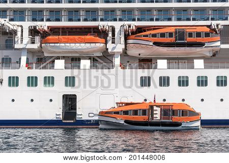 Several lifeboats on large luxury cruiser ready to deploy