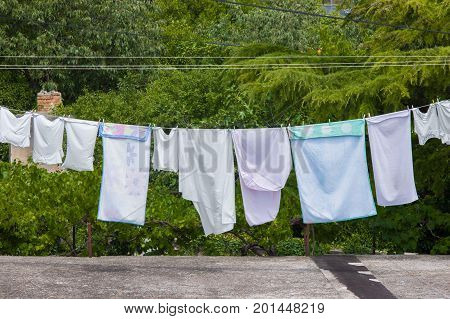 Fresh clean clothes are drying outside in the garden closeup footage
