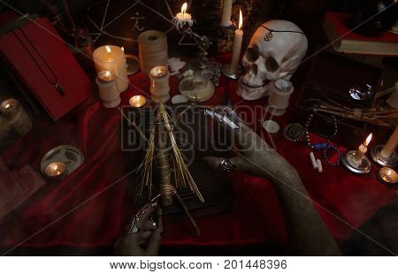 Witchcraft composition with witch's hands carrying out a ritual with Voodoo doll, candles, magic book, tarot cards, crystal, amulets and pentagram symbol. Halloween concept, black magic ritual.