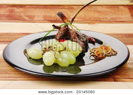served ribs over wooden table with chives and grapes