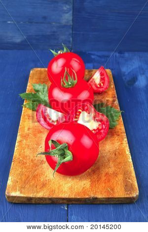 raw vegetables : fresh raw ripe tomatoes on cutting board over blue table
