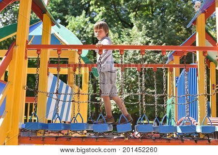 little boy playing on playground in public park