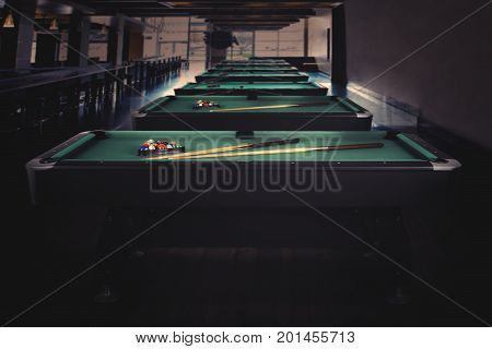 Picture of green billiard table with balls stick and triangle ready to play. shot in the night club