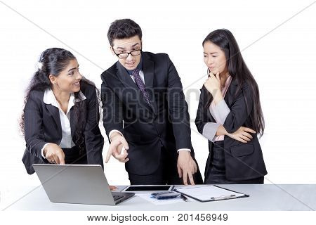 Two business people pointing at a laptop computer while squabbling their friend isolated on white background