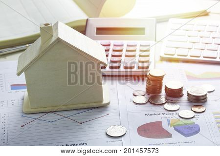 pile of coins and home concept in house finance on wood table
