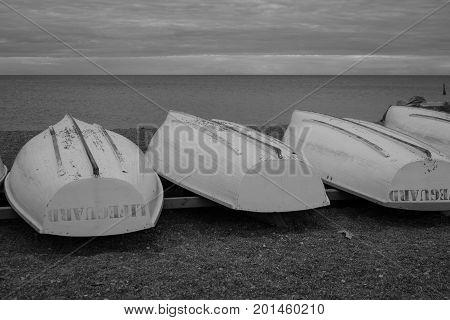 monochrome photo of lifeguard boats ashore at a beach