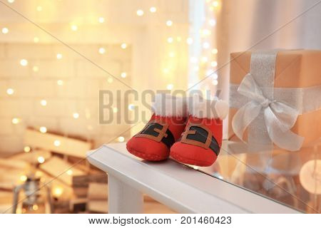 Cute booties for baby on table against blurred Christmas lights