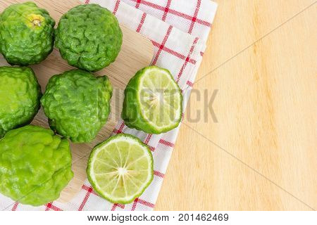 Close up fresh bergamot and bergamot slice on dark wood table background. bergamot on old wooden brown with copy space. (Bergamot or Kaffir lime)