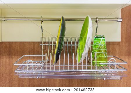 Closeup of Bright dishes and glasses drying on a metal dish rack in kitchen room interior