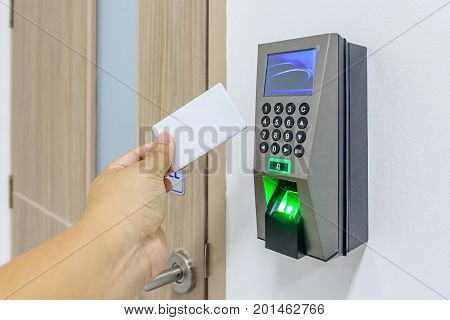 electronic key- card and finger scan access control system to lock and unlock doors Hand Holding Keycard To Open Door