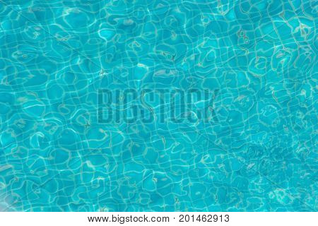 Blue swimming pool rippled water detail Background of rippled pattern of clean water in blue swimming pool