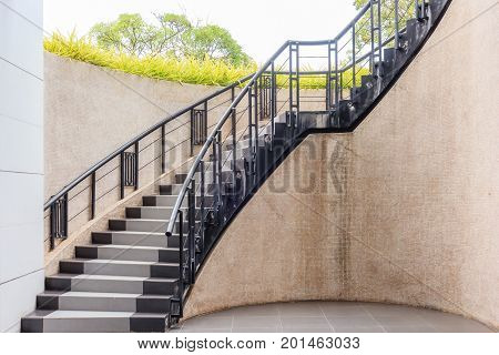 Outdoor stone staircase. Stone steps of old staircase with metal fence. Exterior design in vintage style.