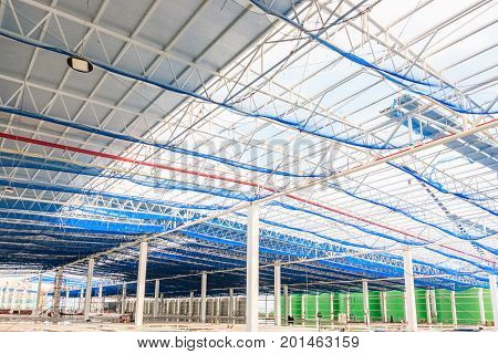 The roof steel structure of a new commercial building under construction against a clear blue sky in the background