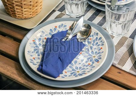 Cutlery set with indigo linen napkin in white plate on a wooden table in a restaurant table setting knife fork spoon glass and plates
