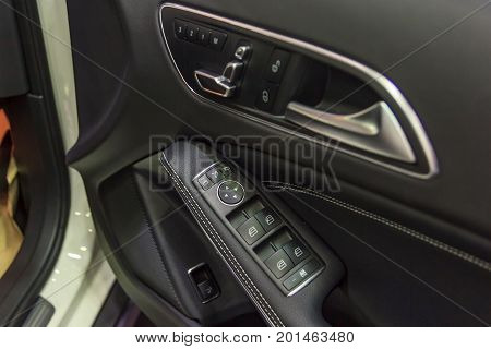 Interior details on buttons controlling the windows and mirror control panel on driver's door detail of modern luxury car