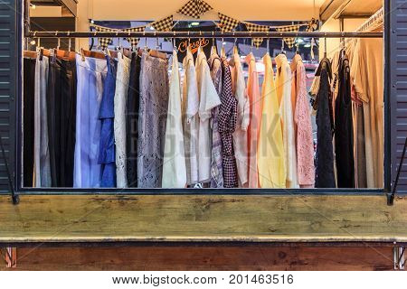 Pastel color female clothes on open cloth rail wooden hanger in department store