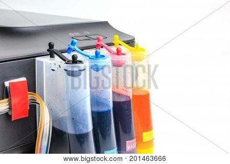 Setting up modified ink tank for inkjet printer. Printer color ink tank beside isolated on white background