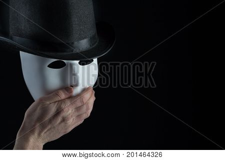 Male hand hiding mouth of white mask wearing black top hat on black background with copy space. Freedom of speech and shock concept