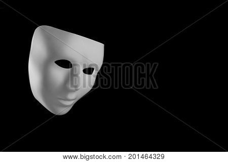 White mask looking down isolated on black background with copy space