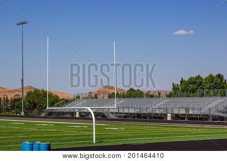 Goal Post On Football Field Next To Bleachers