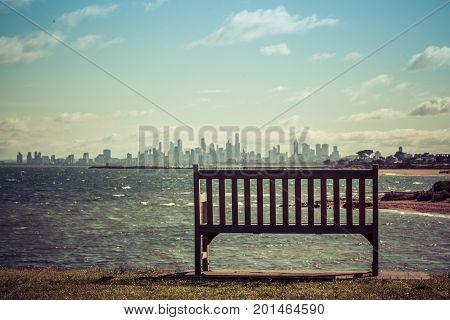 Empty wooden bench on ocean shore overlooking the skyline of Melbourne CBD on bright sunny day