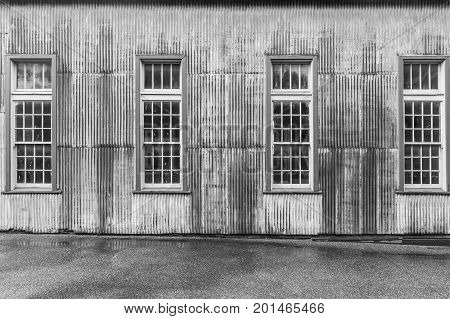 Old rusty metal shed with tall windows closeup in black and white