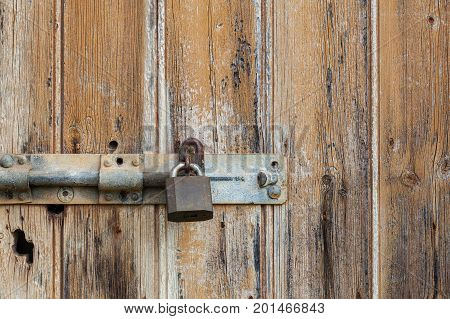 Old grungy weathered wooden door closeup with metal latch and lock background texture