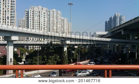 Shanghai, China - Nov 5, 2016: Elevated motorways and high-rise buildings. Chaotic traffic congestion below the motorways.