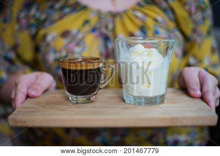 hand of woman holding a cup of Affogato coffee or espresso with icecream on Wooden board and blurred background