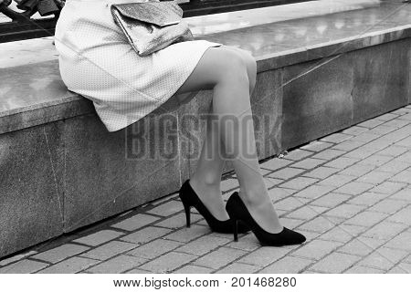 women's high-heeled shoes Girl sitting on street curb