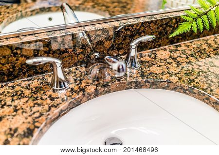 Closeup Of Modern Bathroom Sink With Brown Granite Countertop And Mirror
