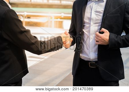 Two confident business man shaking hands for demonstrating their agreement to sign agreement or contract between their firms / companies / enterprises. success dealing greeting and partner concept.