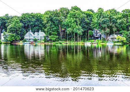 Lake Audubon with lakefront waterfront houses in Reston Virginia with reflection of summer green foliage on trees